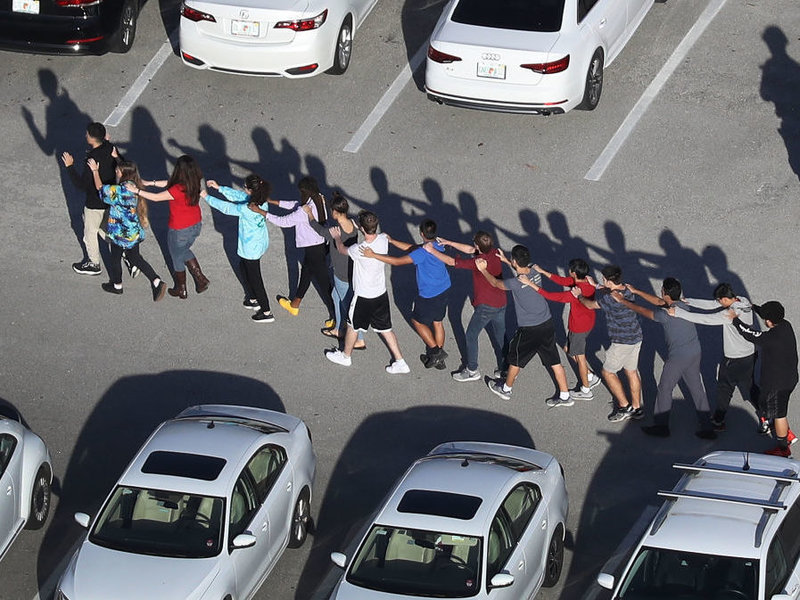 Credit to NPR, a line of students walk with their hands up out of school