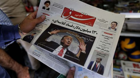 A man takes a glance at a newspaper with a picture of US president Donald Trump on the front page, in the capital Tehran on July 31, 2018. - Iran